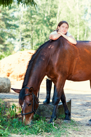 Young teenage cheerful girl equestrian hugging her favorite chestnut horse. Vibrant multicolored summertime outdoors vertical image. Stock Photo