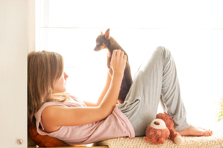 toyterrier: Sweet morning! Young girl in pyjamas holding her lovely Toy-terrier dog in rays of sunlight. Multicolored vibrant horizontal indoors image. Stock Photo