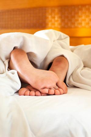pieds sales: Dormir enfant pieds sales sur blanc linge de lit de dos. Intérieur. Banque d'images