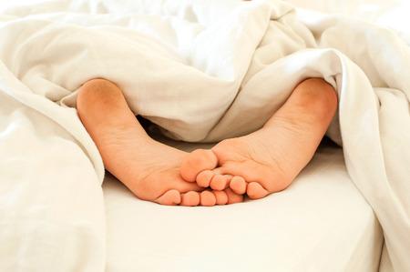 pieds sales: enfant dormir pieds sales fatigués sur des draps blancs de dos. Indoors close-up. Banque d'images