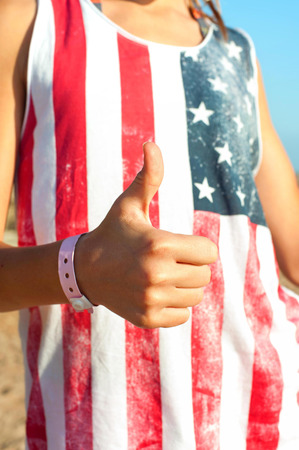 alright: Its alright! Young sunburned girl in american shirt showing thumb up. Summertime outdoors.