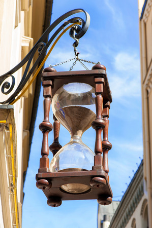 Antique large hourglass hanging in old town on blue sky background. Multicolored vibrant outdoors vertical image. Stock Photo