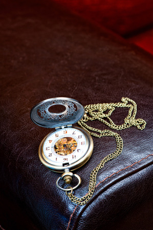 timepiece: Metal elegant antique pocket timepiece on leather background. Indoors close-up. Stock Photo