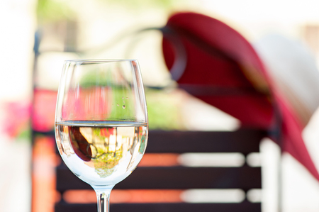 Glass of delicious fresh white wine on wooden table on summer terrace. Colorful outdoors horizontal image.