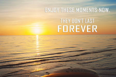 Enjoy these moments now, they dont last forever. Inspirational motivation quote on multicolored summertime sunset beach. Horizontal outdoors image Stock Photo