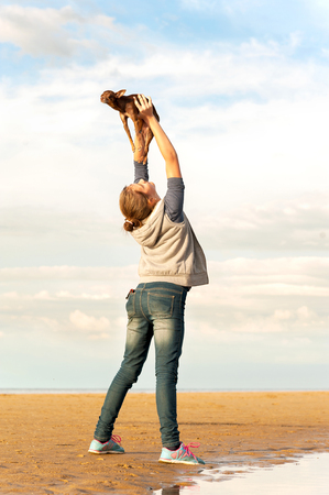 toyterrier: Young cheerful teenage girl holding high up her lovely little Toy-terrier dog. Vibrant summertime outdoors vertical image. Stock Photo