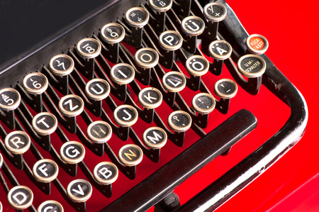 qwerty: Old retro black metallic keyboard with antique round  keys. Horizontal indoors colored closeup image.