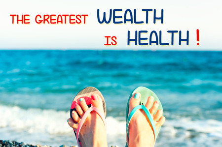 The greatest wealth is health. Motivational inspirational quote with funny cute tidy womans feet on the beach on ocean waves background. Colored horizontal summertime image with vintage filter. Stock Photo