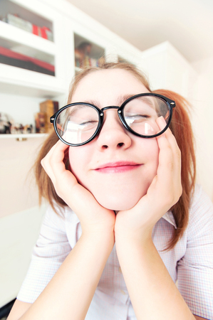 fantasize: Portrait of funny nerdy girl with ponytails in eyeglasses dreaming about holidays with closed eyes in school. Indoors close-up vertical image with filter. Wide angle. Stock Photo