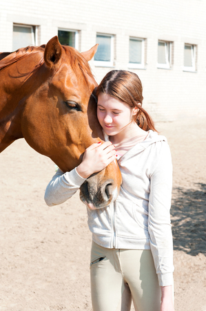 Young cheerful teenage girl equestrian hugging her favorite red horse. Vibrant multicolored summertime outdoors vertical image.