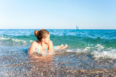 thru: Happy young teenage girl enjoying in sea splashing waves. Inspirational summertime outdoors vibrant horizontal image. Mediterranean Sea.