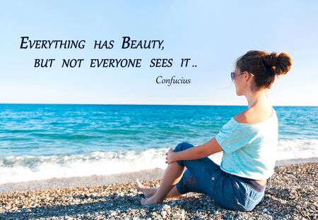 Everything has beauty but not everyone sees it. Inspirational motivation quote with young beautiful girl sitting on ocean coast. Outdoors horizontal summertime image with blue sky and waves background.