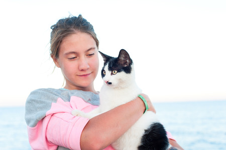 Portrait of tanned teenage girl holding cat on pier. Colored outdoor horizontal image with blue seascape  background.