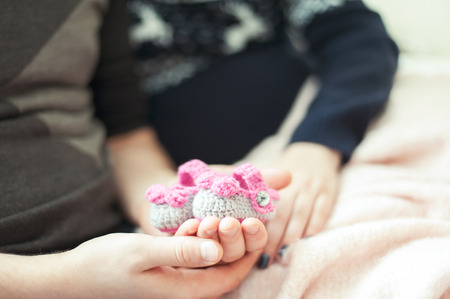 Young happy future parents hands holding woollen knitted newborn baby booties. Indoors horizontal colored close-up image with soft vintage filter. Stock Photo