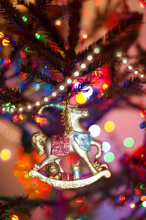 Antique homemade wooden new year horse toy hanging on christmas tree with festive  illuminated background. Vibrant colored indoors vertical image. Stock Photo