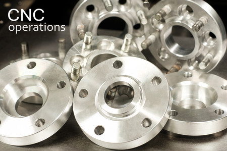 Metal mold of wheel spacers and bolts on dark background with superscription - CNC operations. Milling and lathe industry. Metal engineering. Indoors closeup horizontal image. Stock Photo