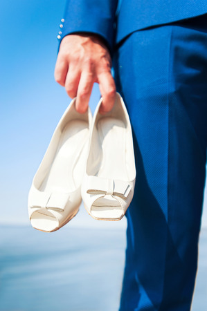 bridegrooms: Bridegrooms hand holding womans white wedding shoes. Vibrant colored summertime outdoors vertical image with filter on blue seascape background. Low point of view.