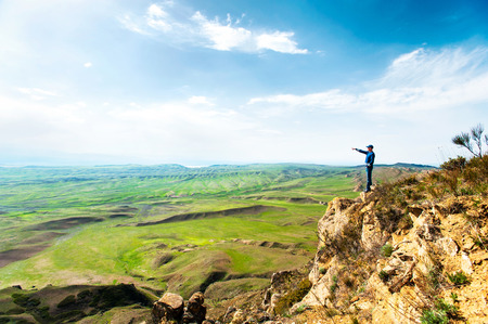 over the edge: Young man at top of rock cliff pointing away by hand on blue cloudy sky background. Summertime colorful horizontal image. Azerbaijan border, David Gareja, Georgia.