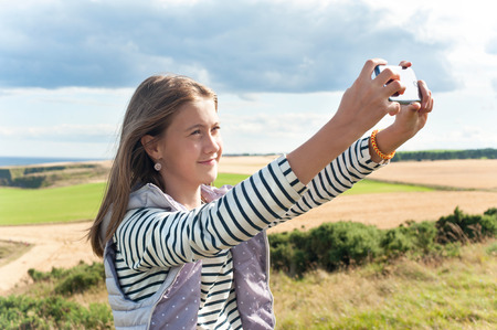 Cheerful young beautiful girl taking self-portrait by smartphone in Scotland Aberdeen and Grampian Highlands. Multicolored summertime horizontal outdoors image.