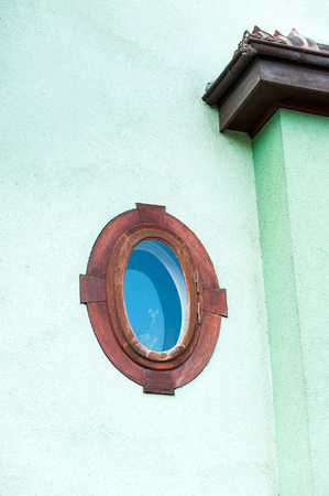 ellipse: Ellipse shaped window in red wooden frame on multicolored green stone wall. France. Vibrant outdoors vertical image. Foto de archivo
