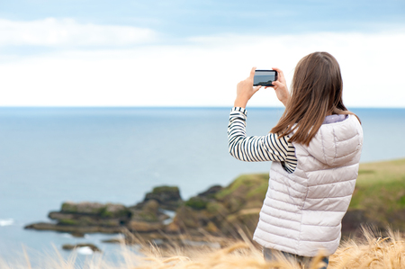 Young beautiful girl traveller taking picture by smartphone in Scotland Aberdeen and Grampian Highlands. View from back side. Multicolored summertime horizontal outdoors image.