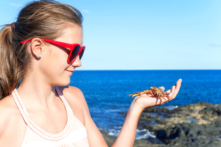 Teenage funny smiling girl in red sunglasses holding an atlantic crab on ocean coast. Blue cloudless sky background. Multicolored summertime outdoors horizontal image.