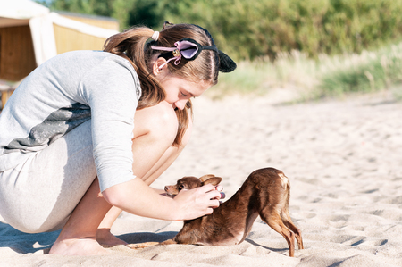Young teenage girl iscratching her lovely dog's back sitting at summer beach. Colored vibrant horizontal outdoors image.