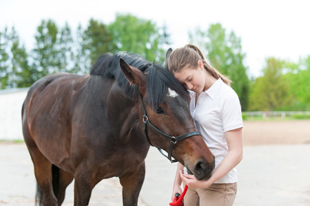 Chestnut horse together with her favorite owner young teenage girl. Colored outdoors horizontal summertime image.