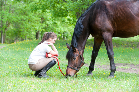 Young teenage girl owner sitting close to her chestnut horse on pasturage green grass. Vibrant multicolored springtime outdoors horizontal image. Archivio Fotografico