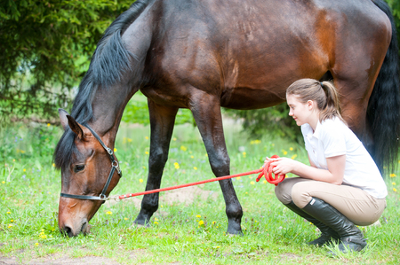 Young teenage girl owner looking tenderly at her favorite chestnut horse sitting on pasturage green grass. Vibrant multicolored springtime outdoors horizontal image.