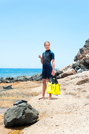 Pretty young lady in diving suit with paddles standing on Atlantic ocean rock coast. Tenerife, Canary islands, Spain. Vibrant multicolored summertime vertical outdoors image.