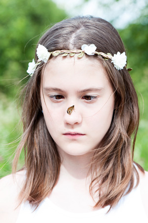 Portrait of pretty cross-eyed boho style girl surprised with butterfly sitting on her nose. Summertime vertical  outdoors image with slightly vintage filter. Stock Photo