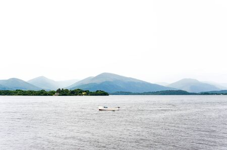 Overcast landscape with early morning rainy weather on Loch Lomond lake in The Trossachs National Park, Scotland, UK. Summertime colored outdoors horizontal image. Stock Photo