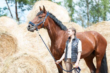 yegua: Joven propietario de adolescente de pie con su hermoso caballo de castaña en el patio de la granja en el heno  paja amarilla rodó pila de antecedentes. Color vibrante al aire libre horizontal imagen de verano. Foto de archivo