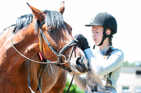 Young teenage girl owner harnessing bay stallion for sport training. Colored horizontal outdoors image.