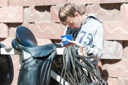 馬術かなり 10 代の少女は、黒の馬革と農場で機器をクリーンアップします。水平の屋外夏のイメージ。