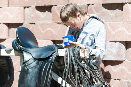 Pretty teenage girl equestrian cleans black Leather Horse Saddle and equipment at farm. Horizontal outdoors summertime image. 版權商用圖片