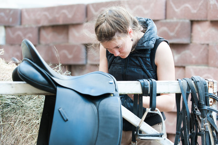 Pretty teenage girl equestrian cleans black Leather Horse Saddle and equipment at farm. Horizontal outdoors summertime image. Stock Photo