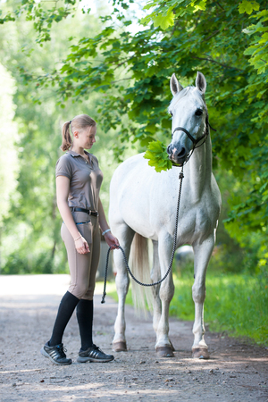 Pretty young blondy cheerful teenage girl equestrian standing with her favorite white horse eating green maple leaves  in summer park. Vibrant colored outdoors vertical image. Stock Photo