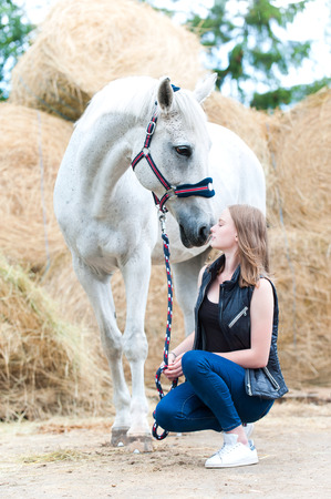 Pretty young teenage girl owner sitting near her favorite white horse at farm yard on yellow haystraw rolled stack background. Vibrant colored outdoors vertical summertime image.