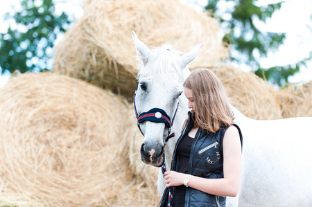 Portrait of pretty young blondy teenage cheerful girl owner with her favorite white horse at farm yard on yellow haystraw rolled stack background. Vibrant colored outdoors horizontal summertime image. Stock Photo