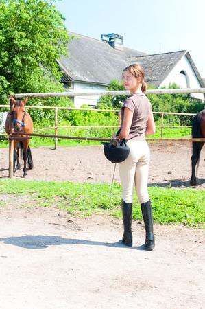 Jeune adolescent équestre debout près du cheval pâturage corral à l'extérieur. Vue de l'arrière. Image verticale d'été multicolore. Banque d'images - 82068555