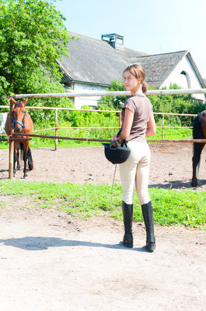 Young teenage girl equestrian standing near horse pasturage corral outdoors. View from backside. Multicolored summertime vertical image.