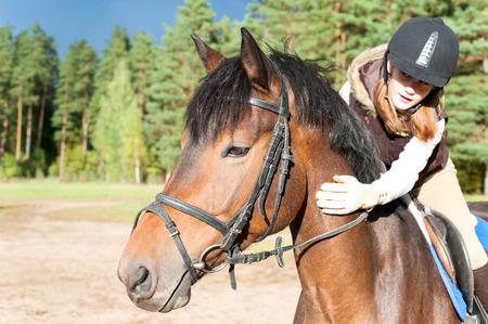 Girl equestrian riding horseback and stroking horse neck. Vibrant summertime horizontal outdoors image. Stock Photo