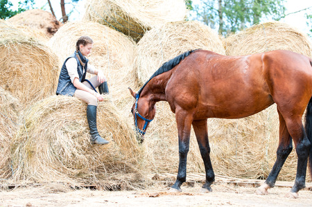Pretty young teenage girl owner sitting on yellow haystraw rolled stack near her favorite bay horse at farm yard. Vibrant colored outdoors horizontal summertime image.