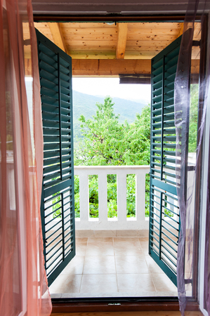 windows frame: Semi-open green wooden shutters on balcony window and spectacular view of the summer mountains. Look from inside to outside. Colored inspiring vertical image. Stock Photo