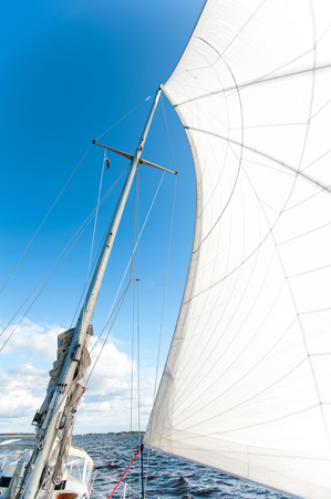 curve: White yacht sails in sunlight on blue cloudy sky background. View from below. Outdoors summertime vibrant colored vertical image.