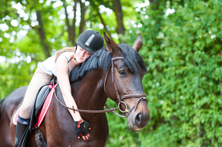 tenderly: Young cheerful teenage girl-equestrian with closed eyes tenderly embracing her big lovely brown horse. Vibrant multicolored summertime outdoors horizontal image.
