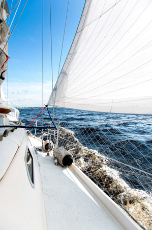 Sailing fast on port tacks through blue sea with water splashing on deck. Outdoors vertical colored image