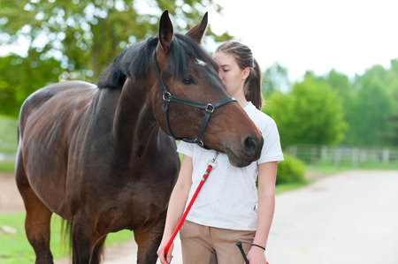 Young teenage lady tenderly kissing her favorite bay horse. Vibrant colored outdoors horizontal summertime image. Stock Photo